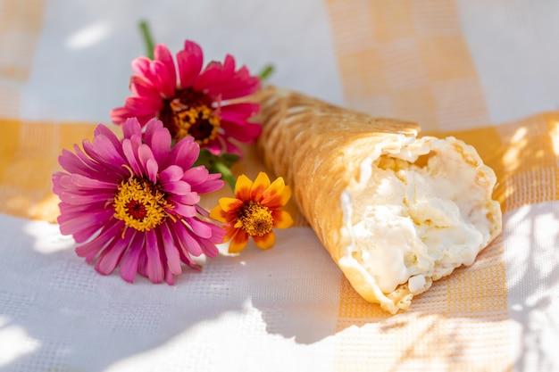 Sorvete artesanal em casquinha de waffle e um pequeno buquê de flores em um guardanapo de linho em um dia quente de verão