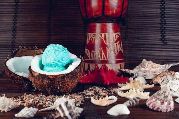 Sorvete azul em uma tigela de coco perto da areia, conchas do mar, estrelas do mar.