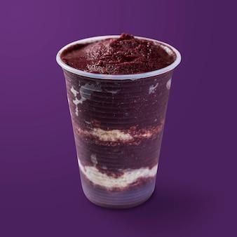 Sorvete brasileiro de açaí e congelado em copo plástico com camadas de flocos de aveia. isolado em fundo roxo. vista frontal do menu de verão.