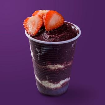 Sorvete brasileiro de açaí e congelado em copo plástico com flocos de morango e aveia. isolado em fundo roxo. vista frontal do menu de verão.
