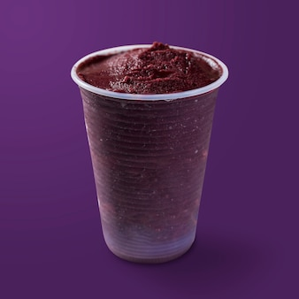 Sorvete brasileiro de açaí e congelado em copo plástico. isolado em fundo roxo. vista frontal do menu de verão.