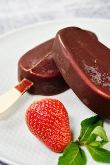 Sorvete coberto de chocolate com morangos e mirtilos em um close-up de placa branca