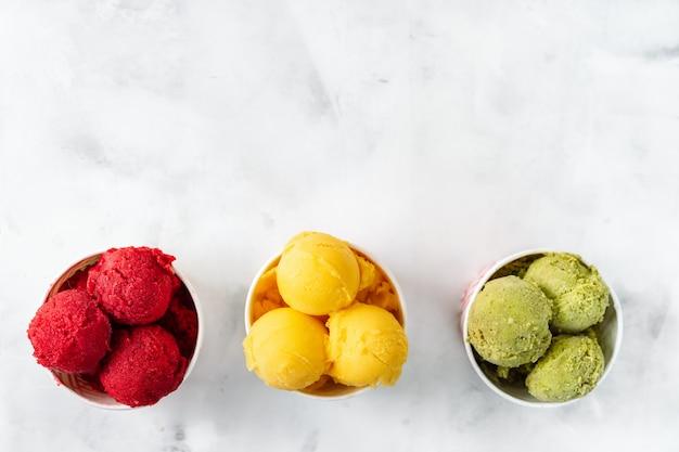 Sorvete colorido de fruta no fundo branco em copos de papel