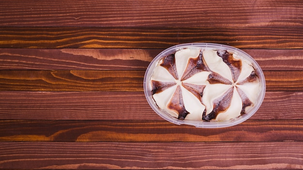 Sorvete com chocolate na tigela de plástico na mesa de madeira