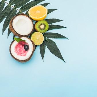 Sorvete congelado dentro do coco cortado ao meio; laranja; kiwi e limão nas folhas contra o fundo azul