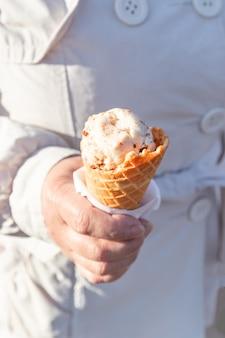 Sorvete de baunilha em um cone crocante, em uma mão feminina