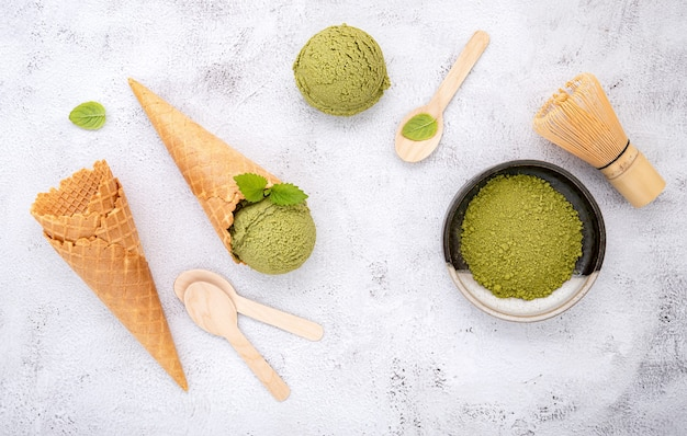 Sorvete de chá verde matcha com cone de waffle e folhas de hortelã em fundo de pedra branca.