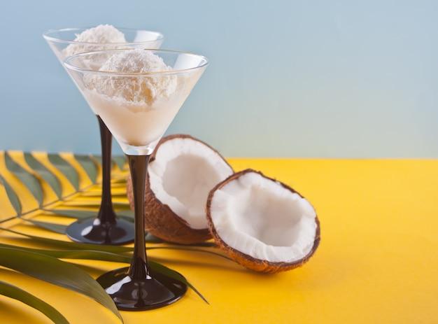 Sorvete de coco na mesa amarela com folha de palmeira e coco