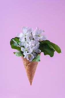 Sorvete de flores brancas em copo de waffle em fundo roxo