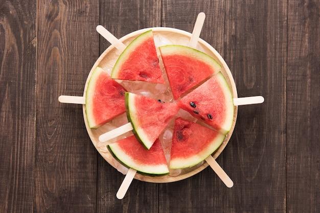 Sorvete de frutas fatiadas de melancia em fundo de madeira