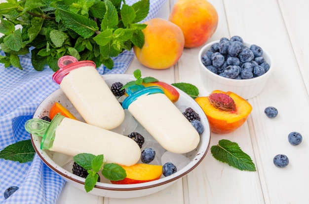 Sorvete de iogurte delicioso dieta com purê de pêssego no palito em um fundo branco de madeira