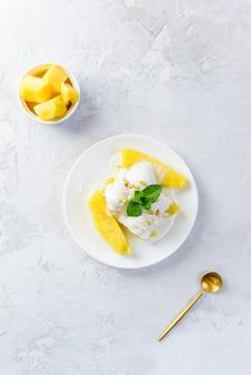 Sorvete de leite de coco com pinhões em rodelas de abacaxi assadas.