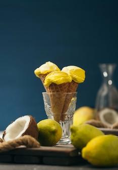 Sorvete de limão amarelo em um chifre de waffle em uma mesa azul e de madeira escura. sorvete de coco e frutas.