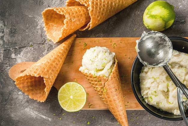 Sorvete de limão refrescante em uma tigela com uma colher de sorvete. com chifres para sorvete (um cheio de sorvete), limão, ralador para descascar. em uma velha mesa de concreto cinza. vista superior copyspace