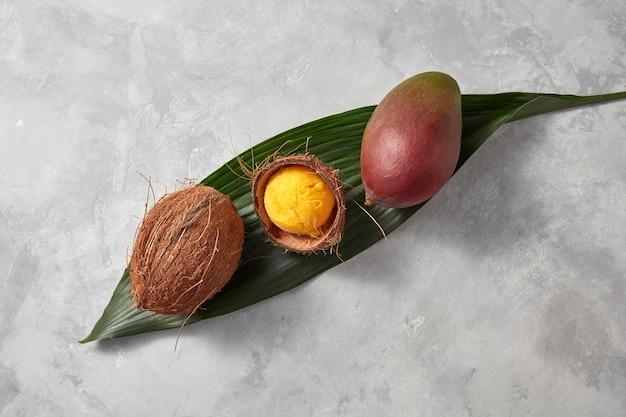 Sorvete de manga caseiro em uma casca de coco em uma folha de palmeira verde com manga inteira e coco em um fundo cinza de concreto com espaço de cópia. vista do topo