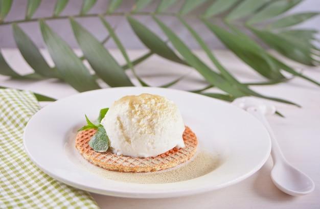 Sorvete de menta no waffle no prato com folha de hortelã e folha de palmeira