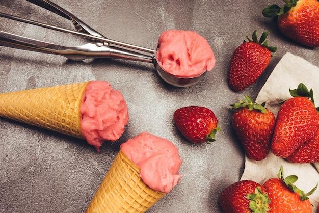 Sorvete de morango em casquinha, colher de sorvete, morangos e frutas vermelhas