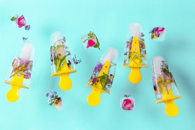 Sorvete de picolés voando com flores e cubos de gelo na mesa pastel