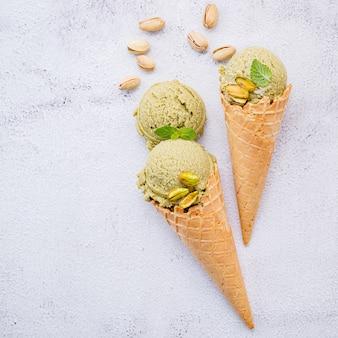 Sorvete de pistache em cones com pistache montado em fundo de pedra branca.