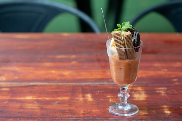 Sorvete de sundae baunilha com bolacha em um copo servido na mesa de madeira na cantina ásia