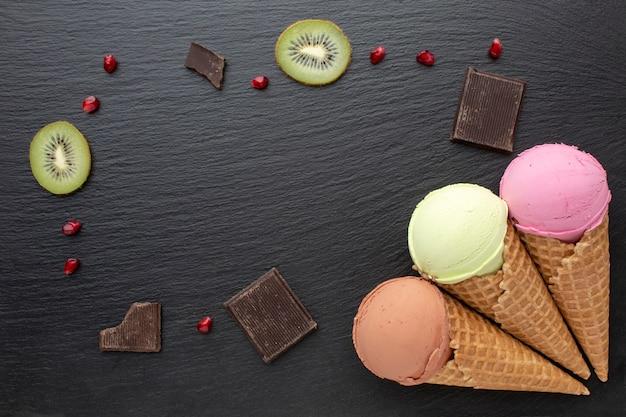 Sorvete em cones com chocolate e kiwi na mesa