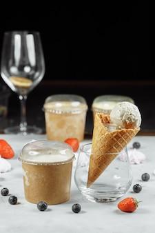 Sorvete em um cone de waffle em uma mesa de luz. o sorvete está derretendo. cones de waffle e morangos