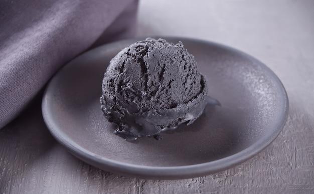 Sorvete preto em uma placa de cerâmica preta com guardanapo cinza sobre uma mesa cinza