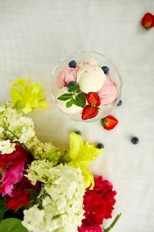 Sorvete saboroso e mirtilos frescos, morango na tigela, apresentado com flores em uma mesa em um jardim durante a temporada de verão para uma festa