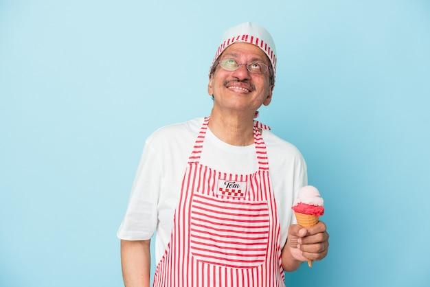 Sorveteiro americano sênior segurando um sorvete isolado em um fundo azul, sonhando em alcançar objetivos e propósitos