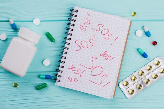 'sos' no caderno e vários comprimidos na mesa de madeira azul. atendimento médico de emergência.