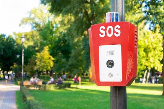 Sos, polícia, botão de emergência no parque público. caixa vermelha com câmera de vídeo e luz azul de advertência no topo