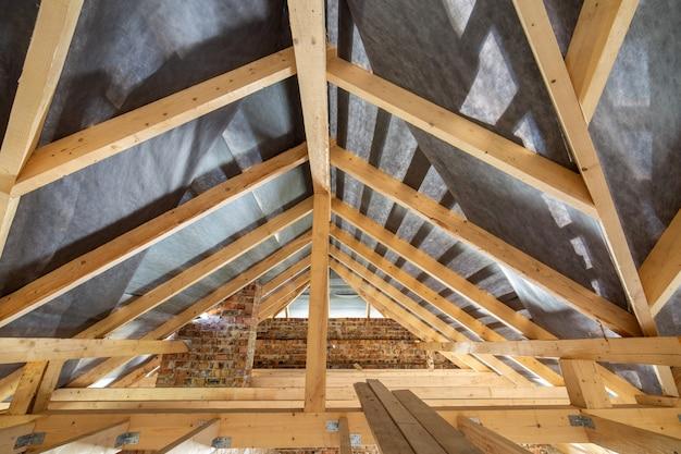 Sótão de um edifício em construção com vigas de madeira de uma estrutura de telhado e paredes de tijolo.