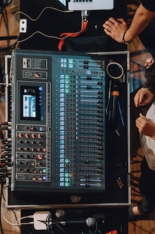 Soundboard profissional incluindo o painel de controle do mixer de áudio com botões e controles deslizantes.