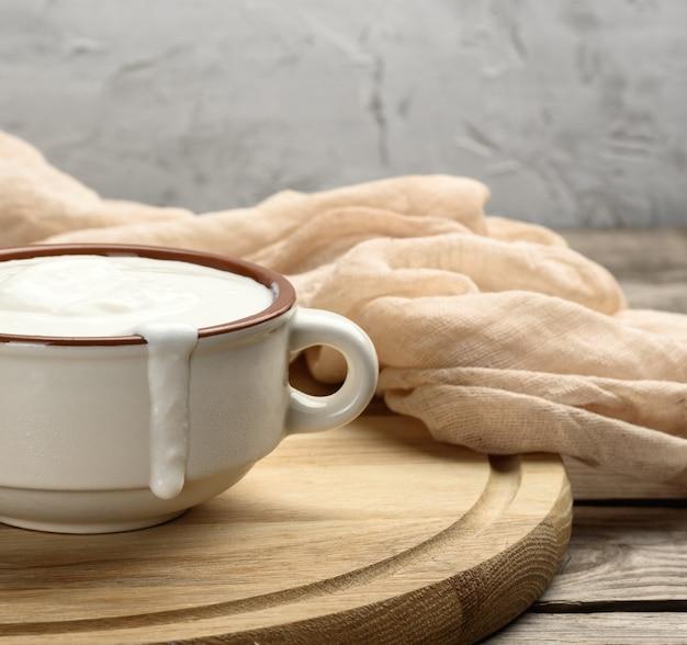 Sour cream em uma tigela de cerâmica marrom com uma colher de pau em uma placa de madeira, produto útil de leite fermentado