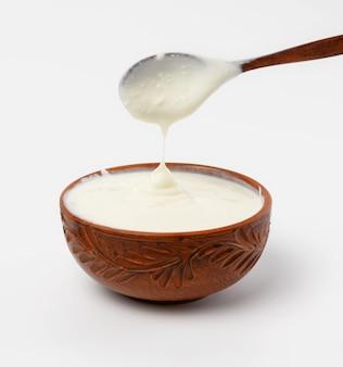 Sour cream em uma tigela de cerâmica marrom com uma colher de pau em uma superfície branca, produto de leite fermentado