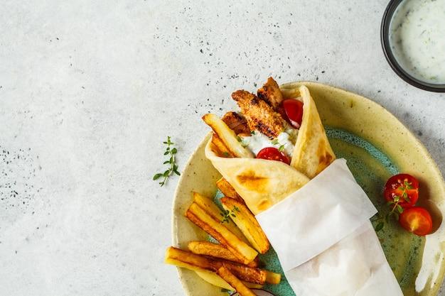 Souvlaki de giroscópios embrulha em pão de pita com galinha, batatas e molho de tzatziki.