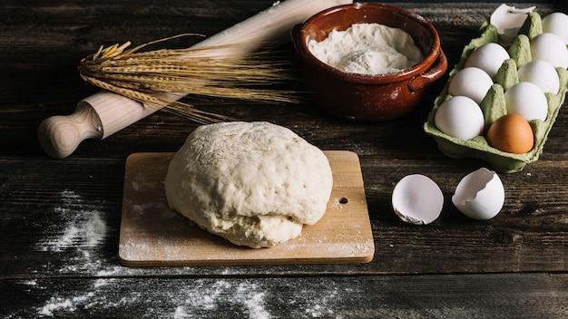 Sove a massa na tábua de cortar com trigo; farinha e ovos na mesa de madeira