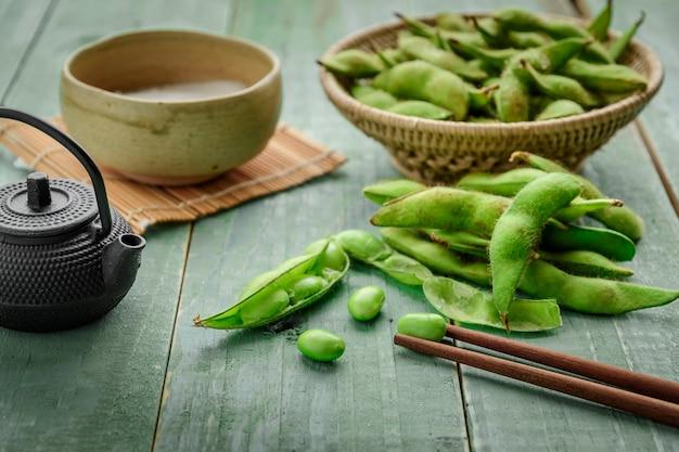 Soybean japonês verde em tigela de madeira na madeira de mesa