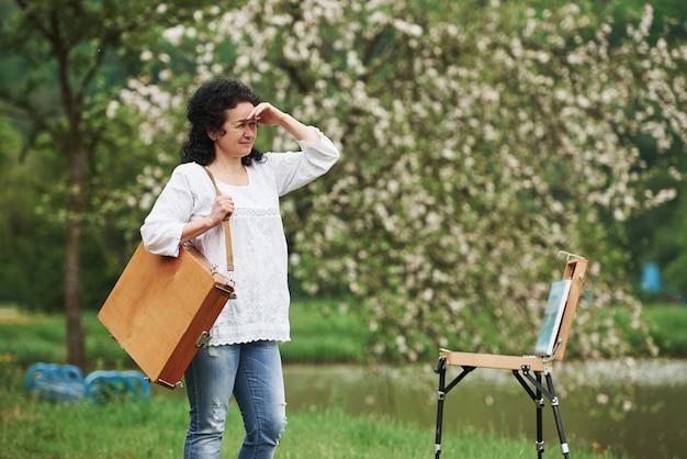Sozinho no parque. pintor maduro com caixa de instrumentos passear