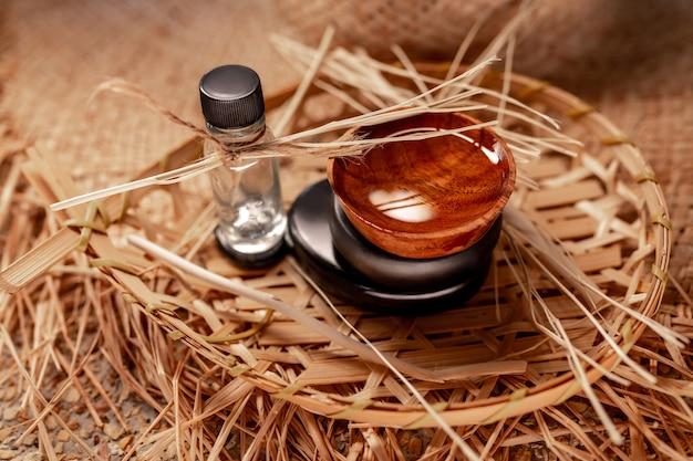 Spa aromático situado na garrafa de cesta de vime com óleo, pires de madeira e pedras zen, close-up