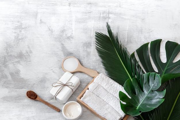 Spa. artigos de higiene corporal em branco com folhas tropicais.