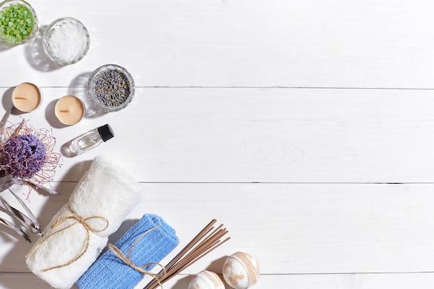 Spa com sal marinho, óleo essencial, sabonete e toalha decorada com flor seca em fundo branco de madeira. vista do topo. copie o espaço. ainda vida. brincar. postura plana