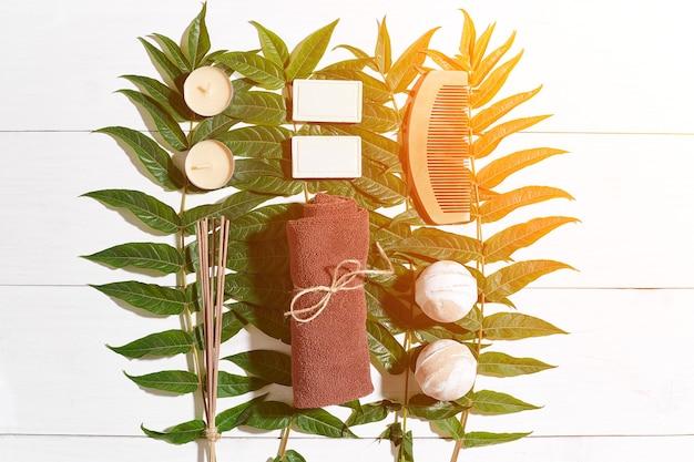 Spa com toalha e sabonete em fundo branco de madeira com folhas verdes. vista do topo. copie o espaço. ainda vida. brincar. postura plana. reflexo solar