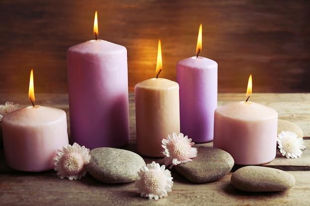 Spa com velas, seixos e flores em fundo de madeira