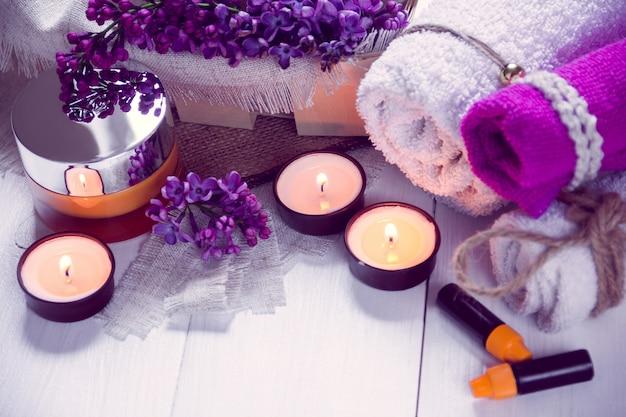 Spa consistem de toalhas, lilás, velas, creme e óleo