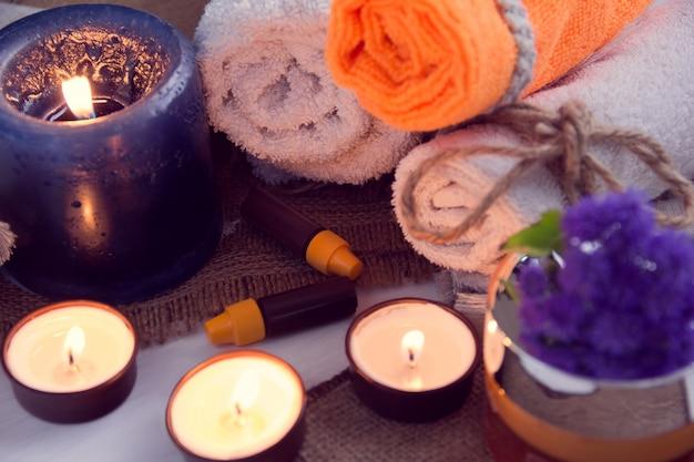 Spa consistem de toalhas, velas, flores, creme e óleo