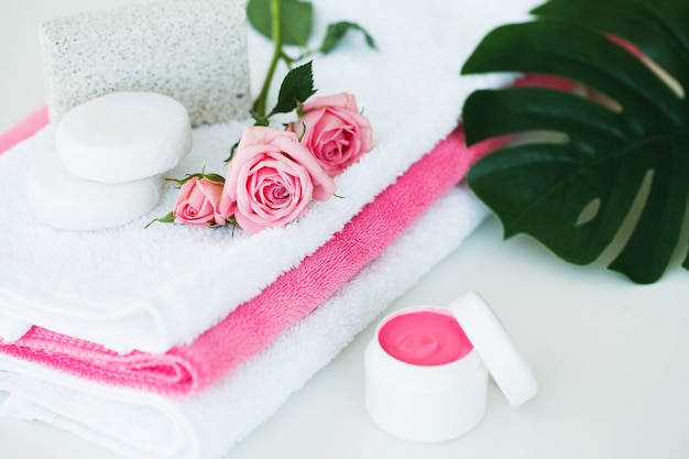 Spa, creme cosmaetic com pétalas de rosa e rosa flor na mesa branca