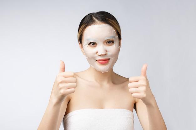 Spa, cuidados de saúde. menina asiática com uma máscara cosmética com apresentando o polegar acima.