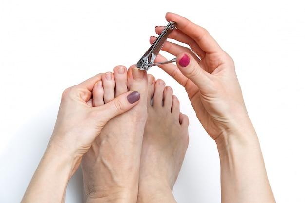 Spa da mulher em casa fazendo pedicure para si mesma, close-up.