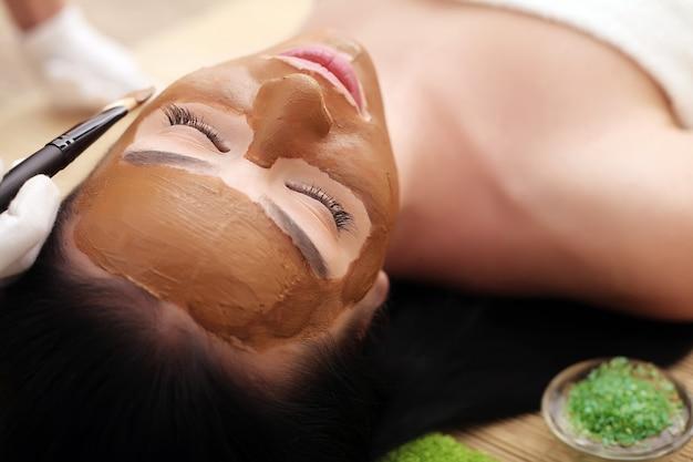 Spa de cosmetologia facial. bela morena em um salão de spa